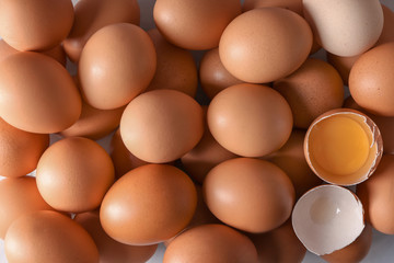 Cracked and whole chicken eggs, top view
