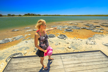 Blonde woman on wooden platform, pointing at Stromatolites on Lake Thetis, a saline coastal lake, Cervantes, Western australia. Tourist enjoys of Australian landscape. Sunny with blue sky.