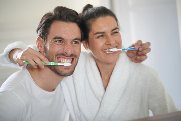 Fun attractive couple brushing teeth together