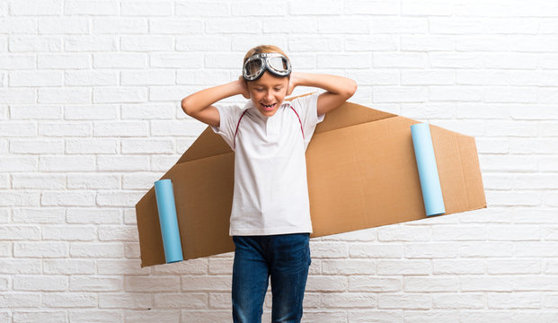 Boy playing with cardboard airplane wings on his back covering both ears with hands