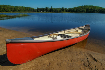 Large red canoe onshore of  lake