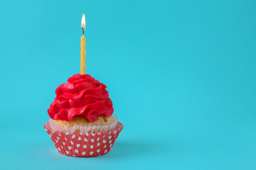 Tasty cupcake with burning candle on color background