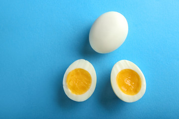 Whole and cut boiled eggs on color background