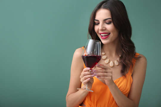 Beautiful young woman with glass of wine on color background