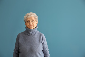 Portrait of senior woman on color background
