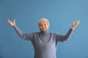 Portrait of elderly woman after making mistake on color background