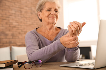 Senior woman suffering from pain in wrist while sitting at table with laptop