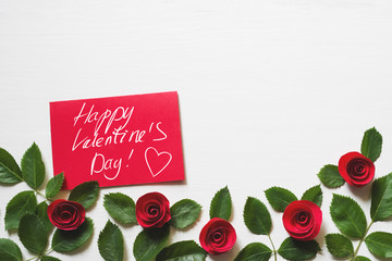 """Red card with an inscription """"Happy Valentines day"""" and decorative roses on a white wooden background. Romantic background by St. Valentine's Day"""