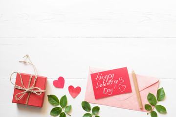 """Red card with an inscription """"Happy Valentines day"""", hearts, gift box and pink envelope on a white wood background, top view. Romantic background by St. Valentine's Day"""