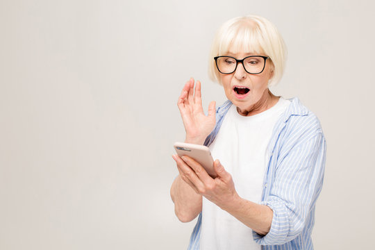 Wow! Phone conversation. Surprised aged woman using phone, isolated over white background.