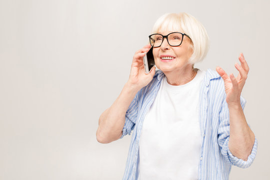Phone conversation. Positive happy aged woman smiling while talking on the phone, isolated over white background.