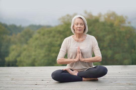 Serene senior woman meditating outdoors