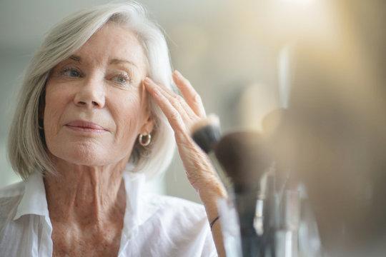 Attractive senior woman looking in the mirror