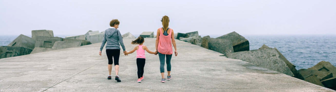 Back view of three female generations walking by sea pier