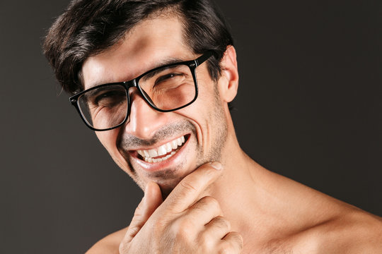 Young man isolated over dark background wearing eyeglasses.