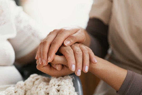 Closeup of hands of a young woman holding hand of an senior lady
