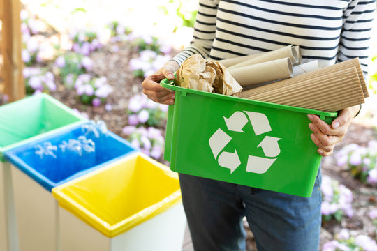 Close-up of a green basket with a recycling symbol with papers held by a woman