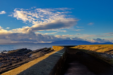 Sunset Reflecting off the of Old Saltcoats Sea Defences with Arran in the Hazy Distance on the Clyde in Scotland.