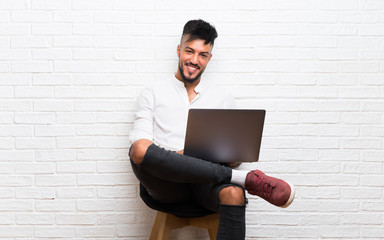 Arabic young man with laptop sitting on a chair