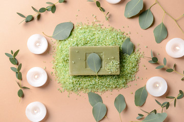 Burning candles with eucalyptus leaves, sea salt and soap bar on color background Wall mural