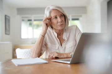 Elderly woman working on computer at home