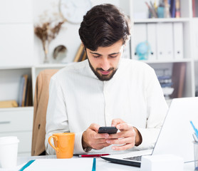 Office worker using his smartphone