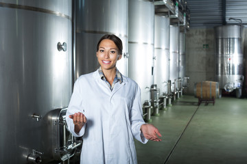 Female in uniform standing in winery compartment