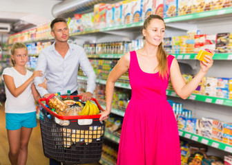 family of three choosing food in the grocery shop