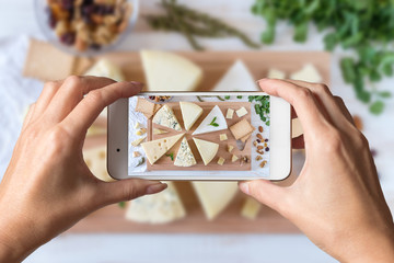 Woman hands taking a photo of different kinds of delicious cheese with nuts and herbs on white table.