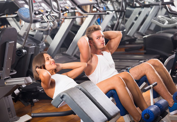 man and woman doing abs exercise in gym .]