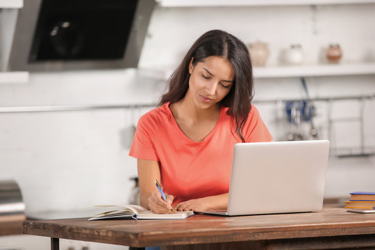 Young woman working with laptop in kitchen