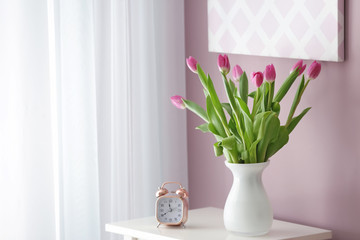 Vase with beautiful tulips and alarm clock on white table