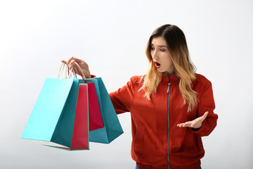 Shocked young woman with shopping bags on white background
