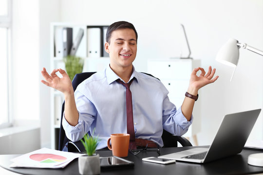 Businessman with a lot of work to do meditating in office