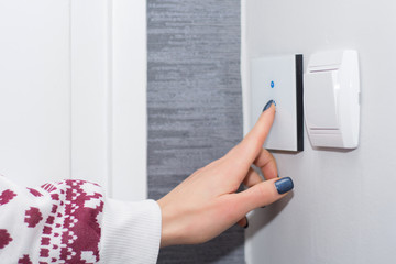 Girl hand turn off light on smart touch switch. Modern light switch with wifi function. Smart house concept. Close up, selective focus
