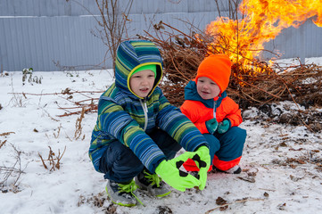 Happy children in winter in warm clothes are looking at fire in snow on the village yard. Children are happy on holiday in village.