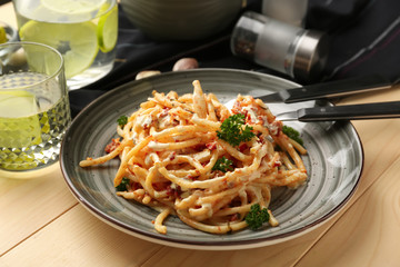 Plate with delicious pasta on wooden table, closeup