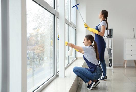 Janitors washing window in office