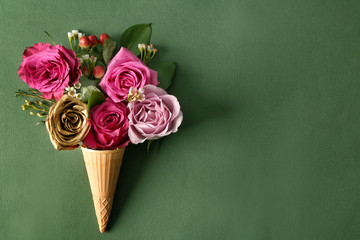 Waffle cone with beautiful roses on color background