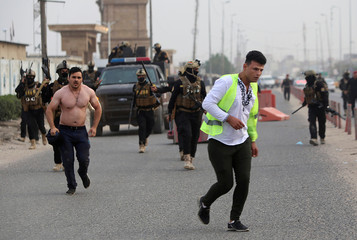 Iraqi demonstrators are seen near Iraqi security forces during an anti-government protest near the government building in Basra
