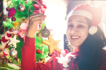 Beautiful young woman in Santa hat decorating Christmas tree at home
