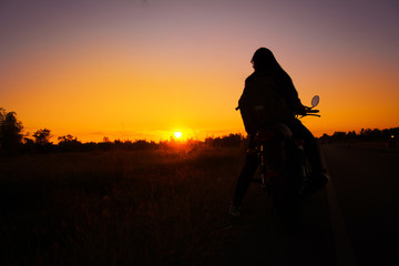 Silhouette of young woman drive with motorbike on street, enjoying freedom and active lifestyle, having fun on a bikers tour.