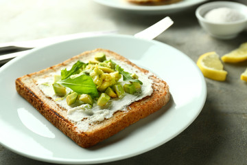 Delicious toast with avocado on plate, closeup