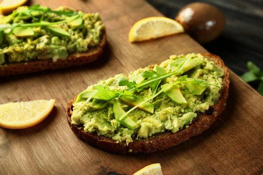 Delicious avocado toasts on wooden board, closeup