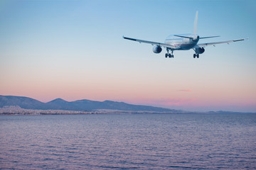 Airplane flying over the sea and beach at sunset. Travel concept.