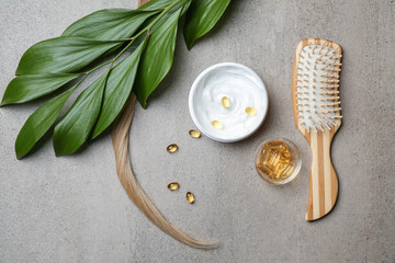 Flat lay composition with natural cosmetics for hair on grey background
