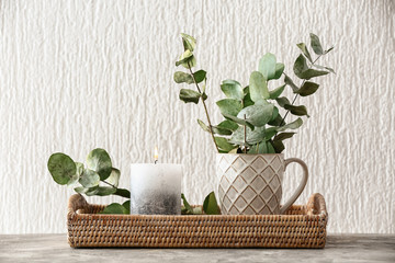 Fototapeta Wicker tray with burning candle and eucalyptus branches on table obraz