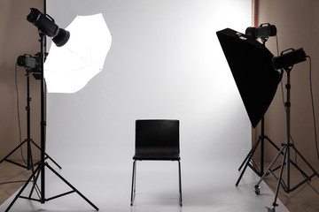 Interior of modern photo studio with professional equipment and chair