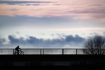 People in silhouette standing on a bridge over a sea