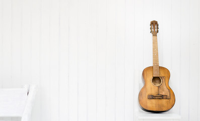 Guitar on a white chair and white background.